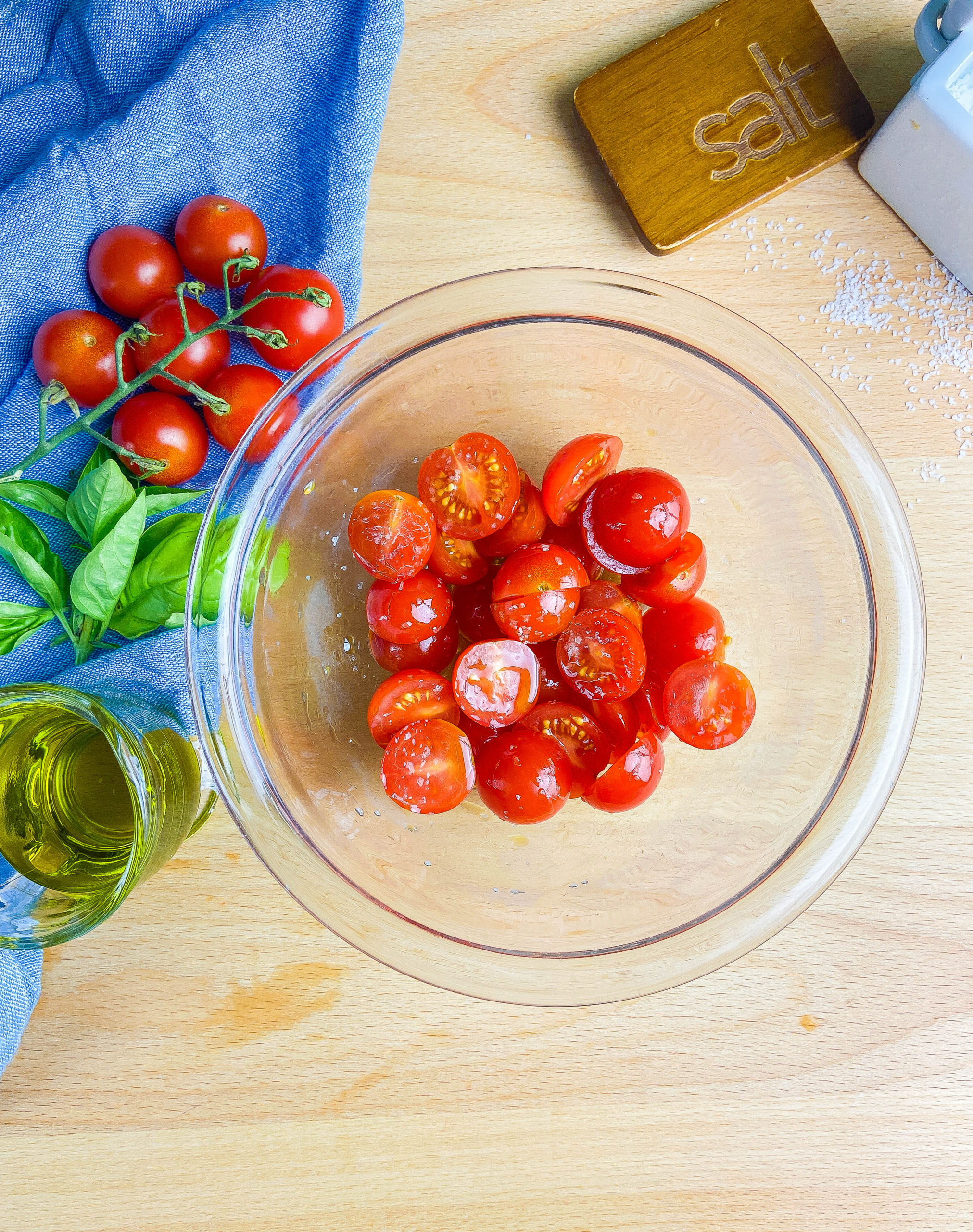 Overhead photo of cherry tomatoes in a glass bowl on a wooden cutting board. Olive oil, basil and tomatoes on a blue towel.