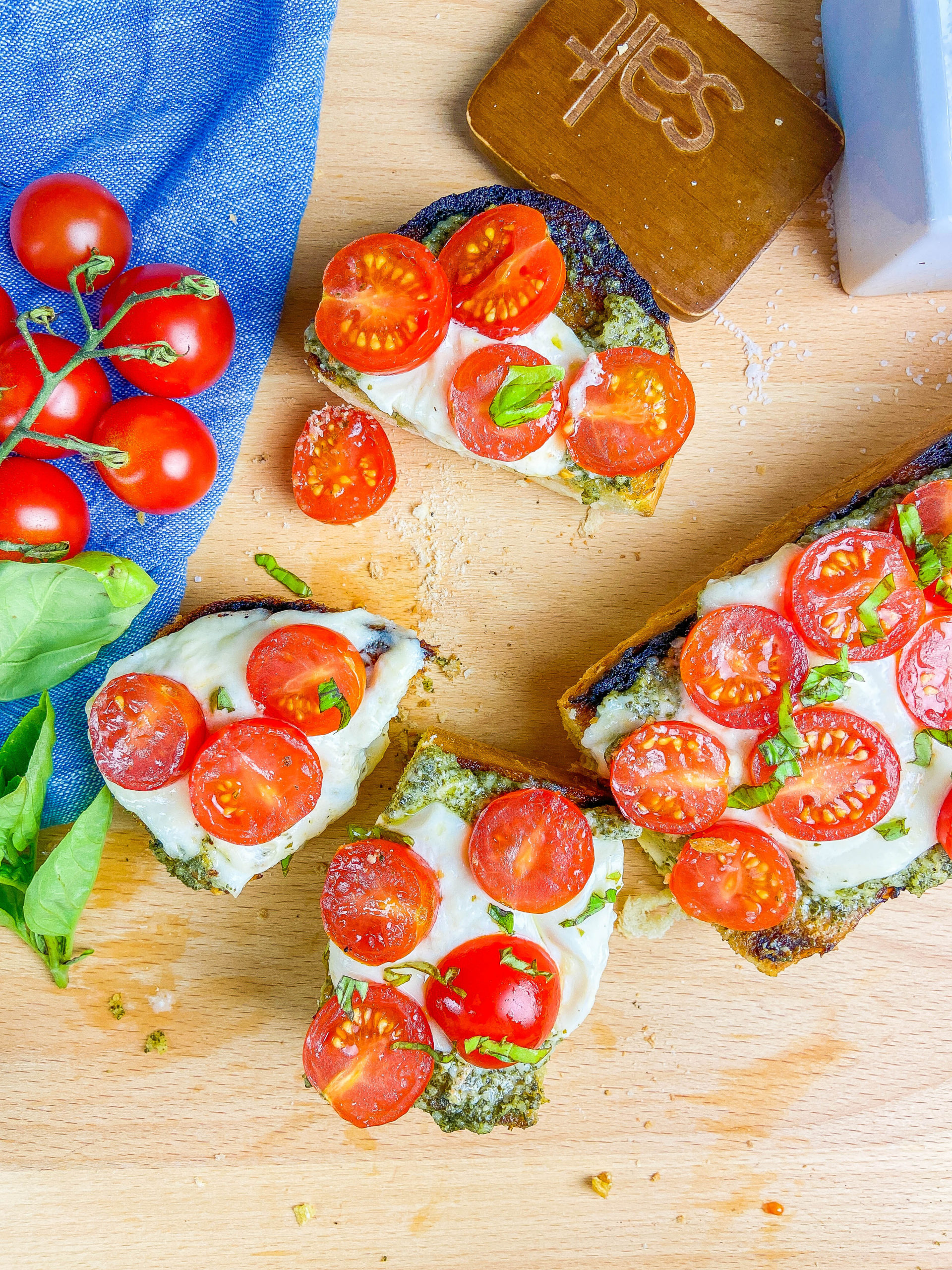 Overhead photo of slices of caprese cheese bread on a wooden cutting board.