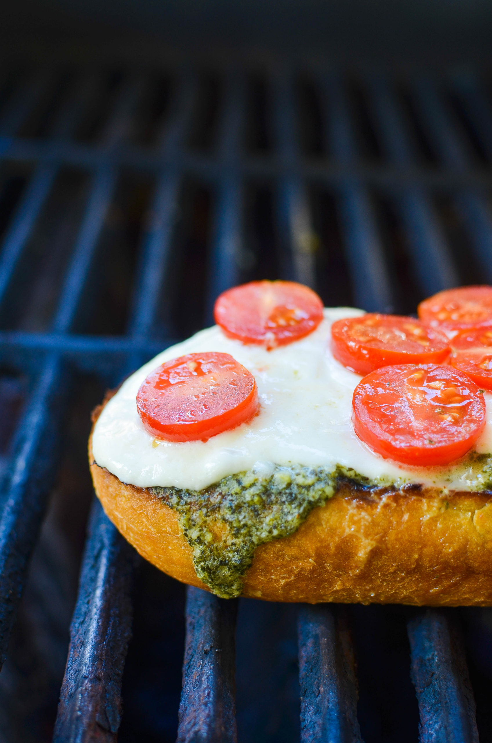 Bread on a grill with pesto, burrata and tomatoes