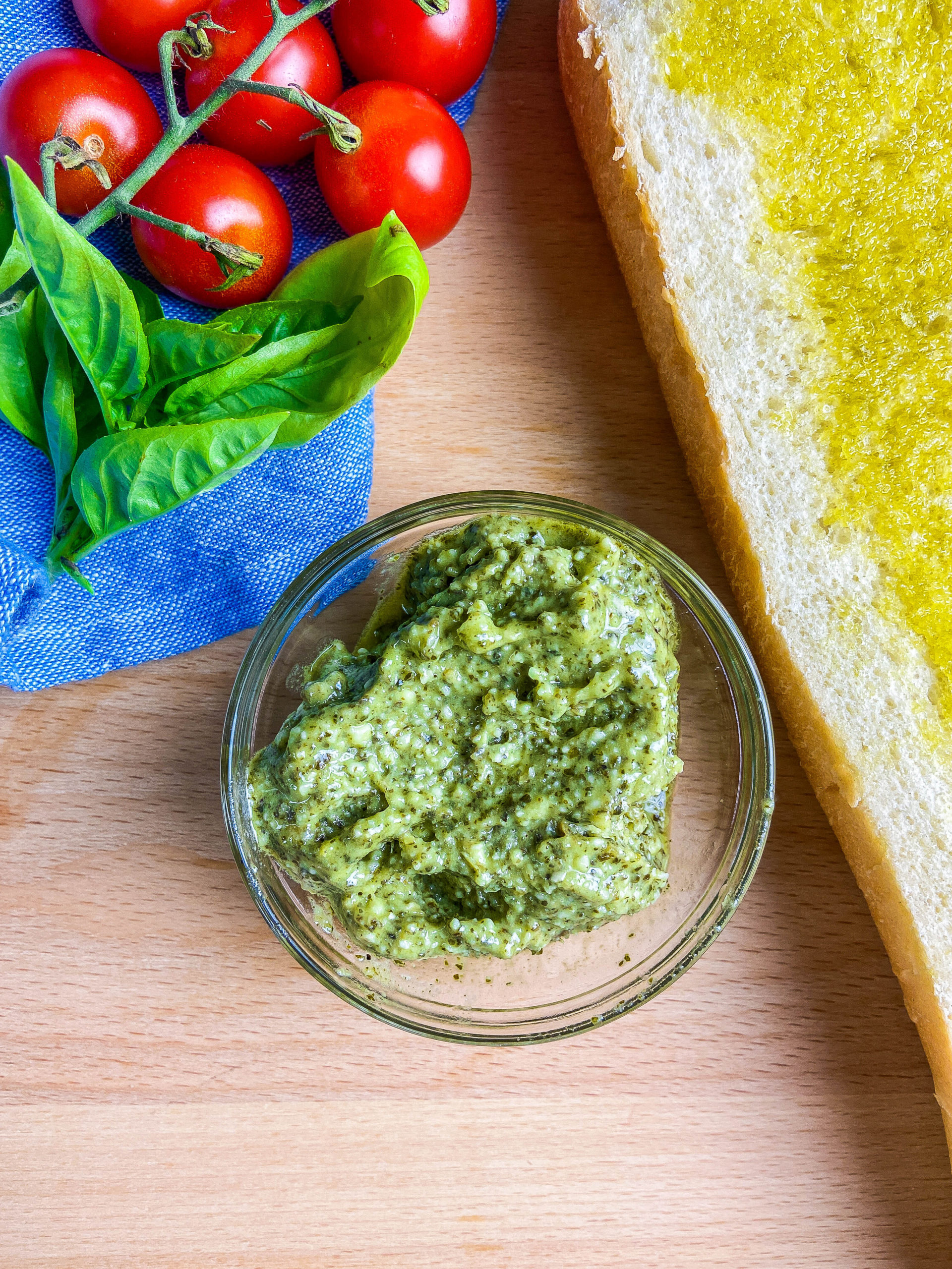 Overhead photo of pesto in a clear glass bowl. Loaf of bread, blue towel, basil and tomatoes on a wooden cutting board.