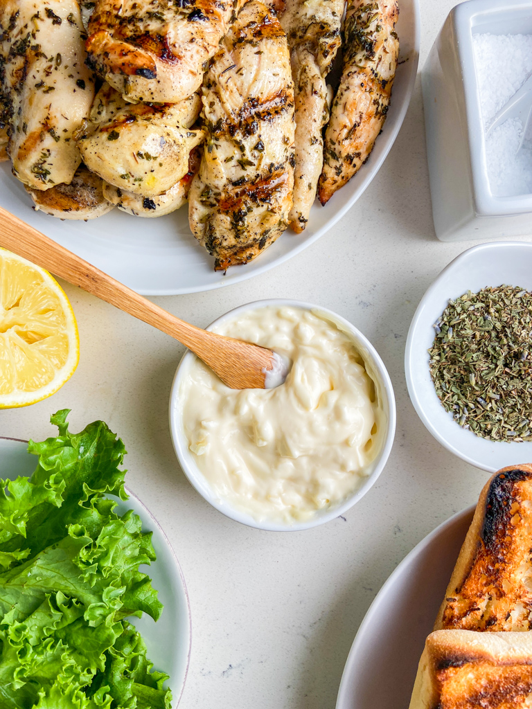 Overhead photo of garlic mayonnaise in a white bowl with a wooden spoon.