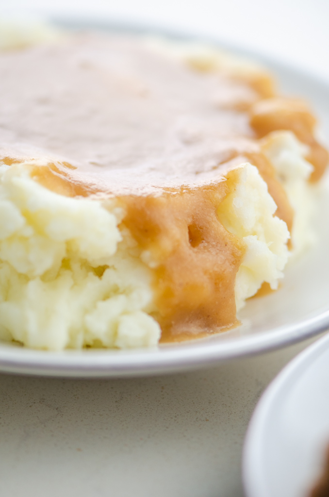 Close up side photo of mashed potatoes with gravy.