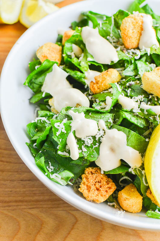 Caesar dressing drizzled over romaine lettuce with croutons, lemons. On a wooden cutting board.