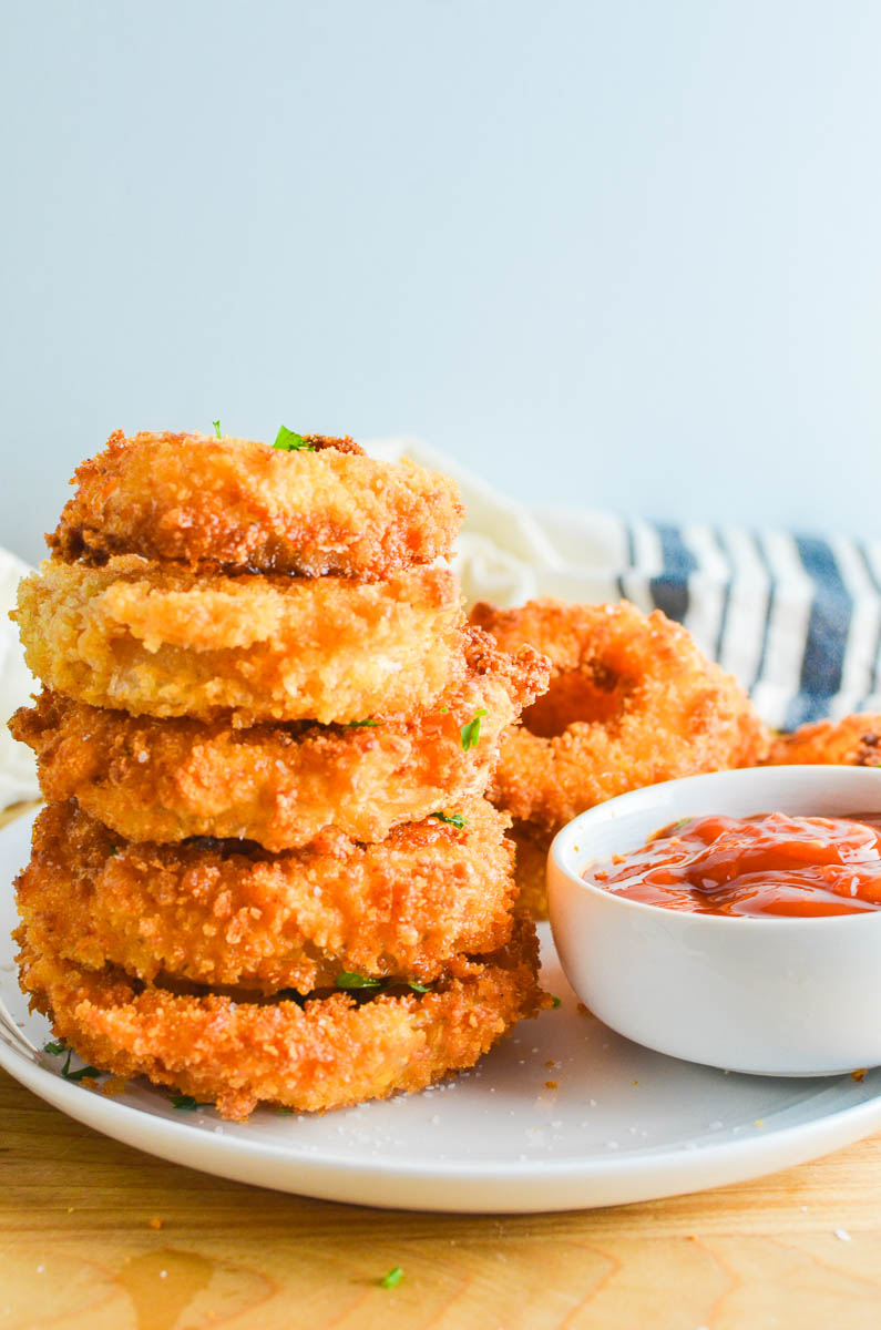 A stack of fried onion rings on a white plate with ketchup and light blue background.