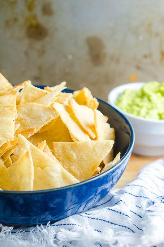 Homemade tortilla chips in a blue bowl.