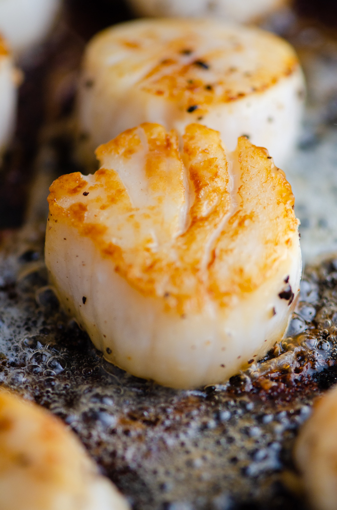 Close up photo of scallop searing in a cast iron skillet.