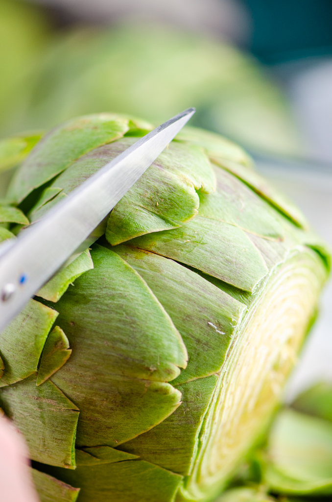 Trimming the leaves of an artichoke with scissors.