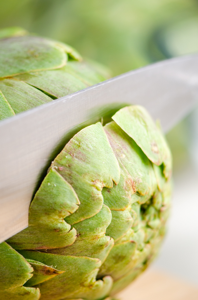 Cutting the top of a raw artichoke with a knife.