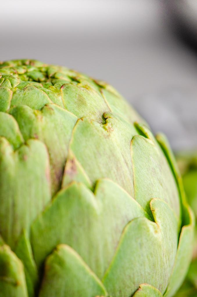 Close up photo of whole raw artichoke.