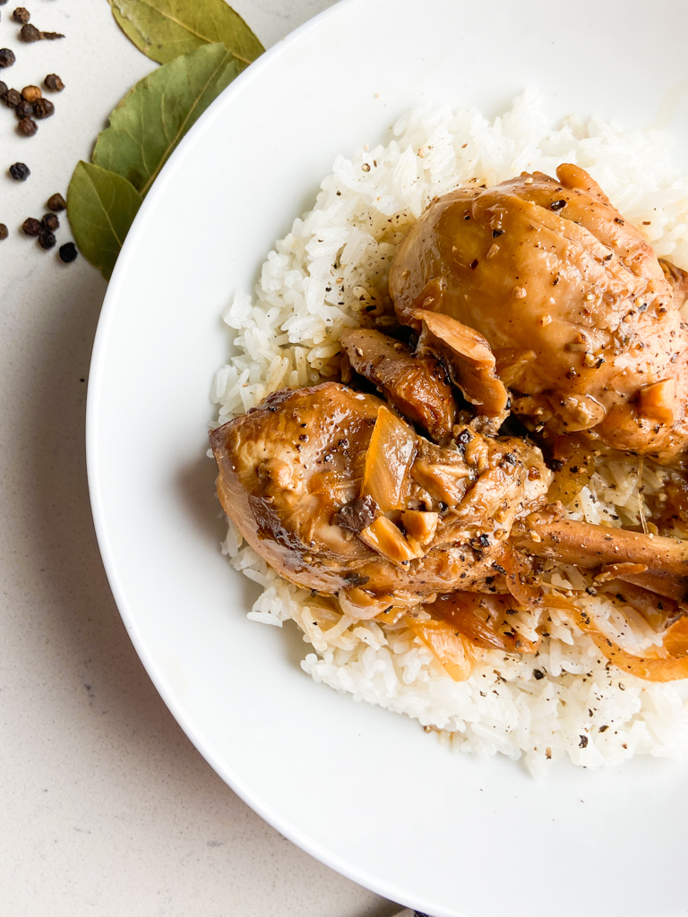 Closeup overhead photo of chicken adobo in white bowl.