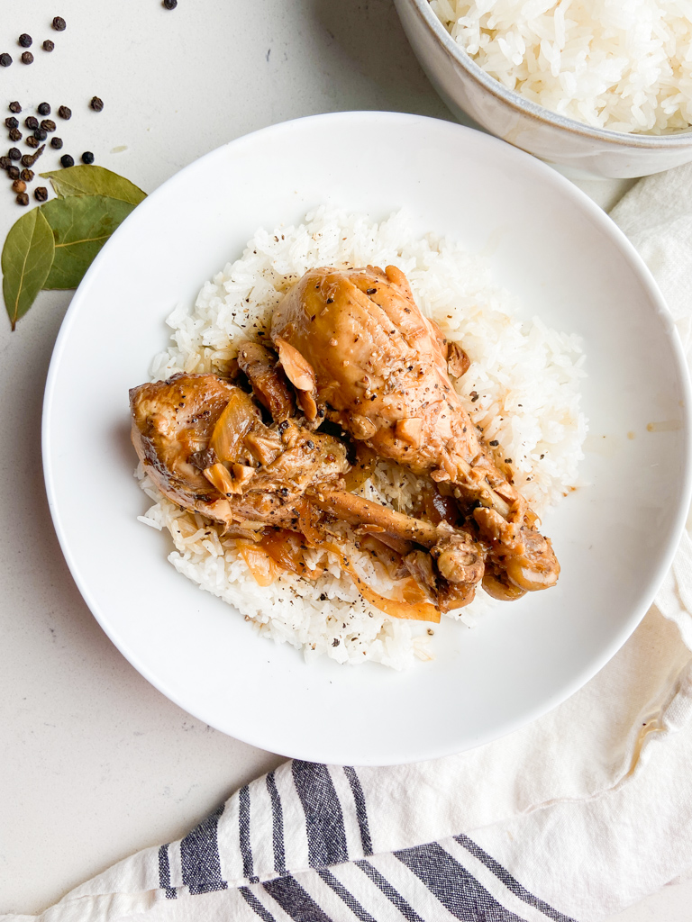 Overhead photo of chicken adobo in a white bowl with rice.