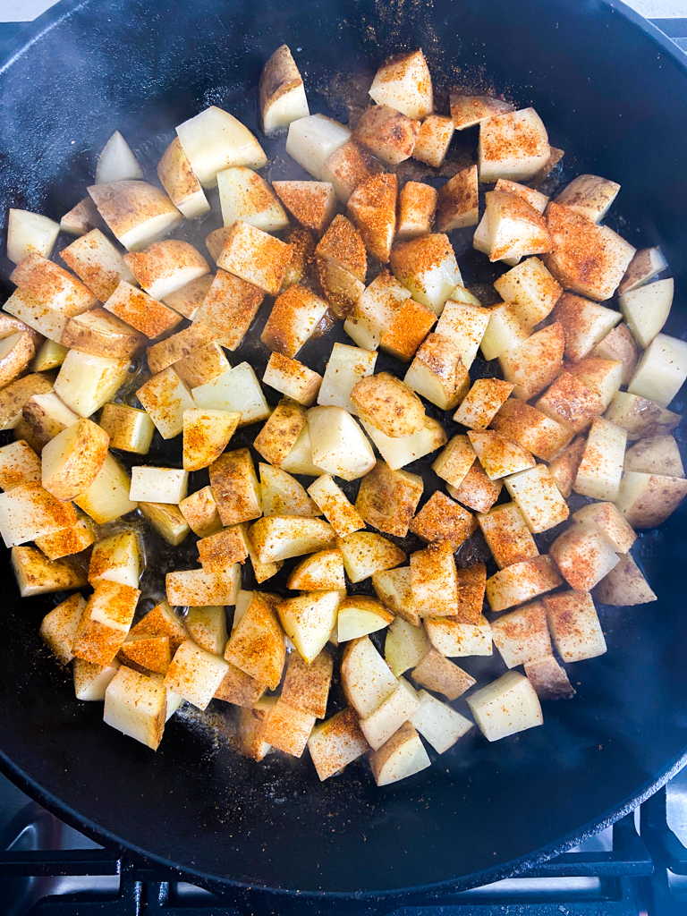 Frying potatoes in a cast iron skillet with Old Bay Seasoning sprinkled on top.