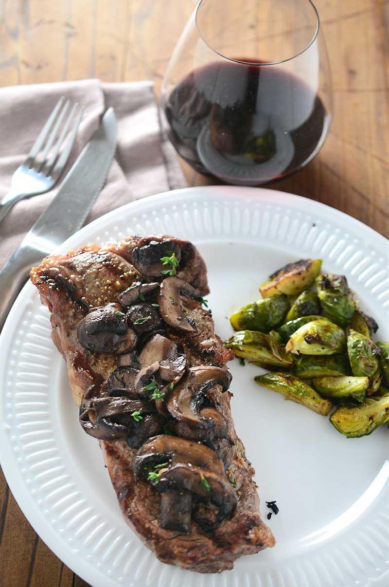 Perfectly grilled New York Strip steak smothered with red wine mushrooms.