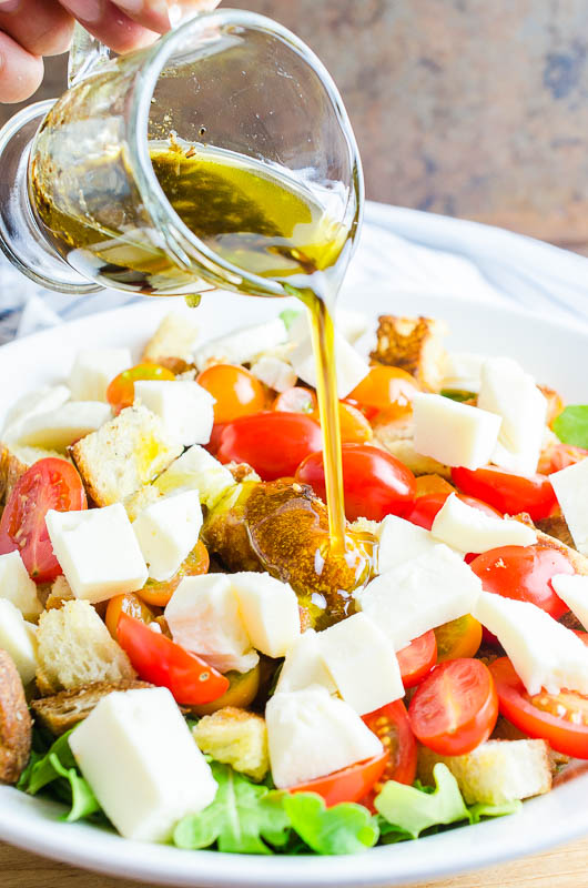 Pouring balsamic vinaigrette on panzanella salad.