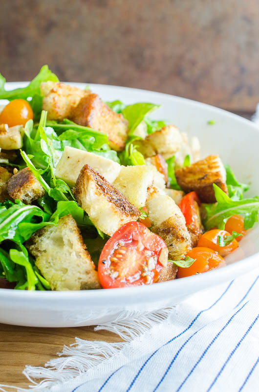 Panzanella Salad is a Tuscan salad with bread, tomatoes, herbs and a simple vinaigrette. It's the perfect way to enjoy summer tomatoes!