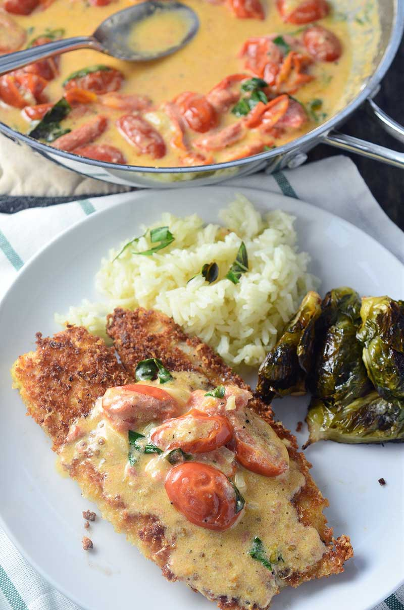 Parmesan crusted tilapia with tomato-basil cream sauce is a quick and easy dinner recipe that the whole family will love. Pan fried tilapia with Parmesan and panko breading, is topped with a delectable creamy tomato-basil sauce.