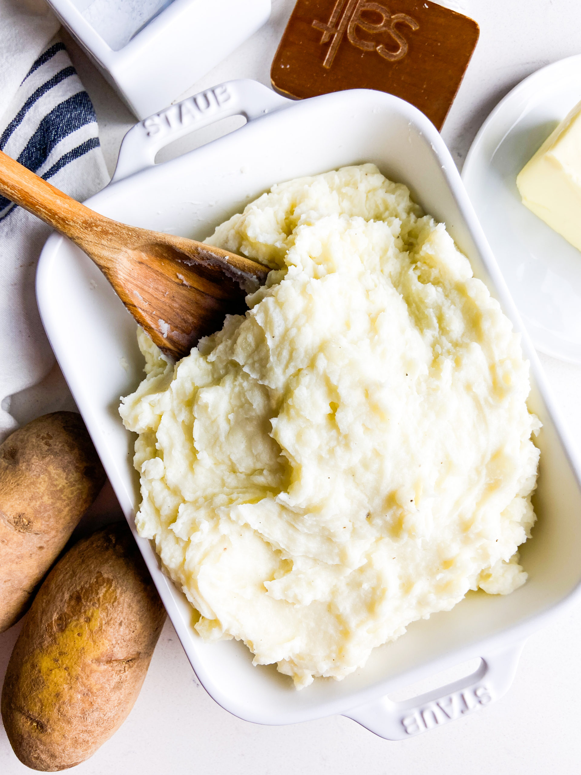 Overhead photo of mashed potatoes in a white dish with wooden spoon.