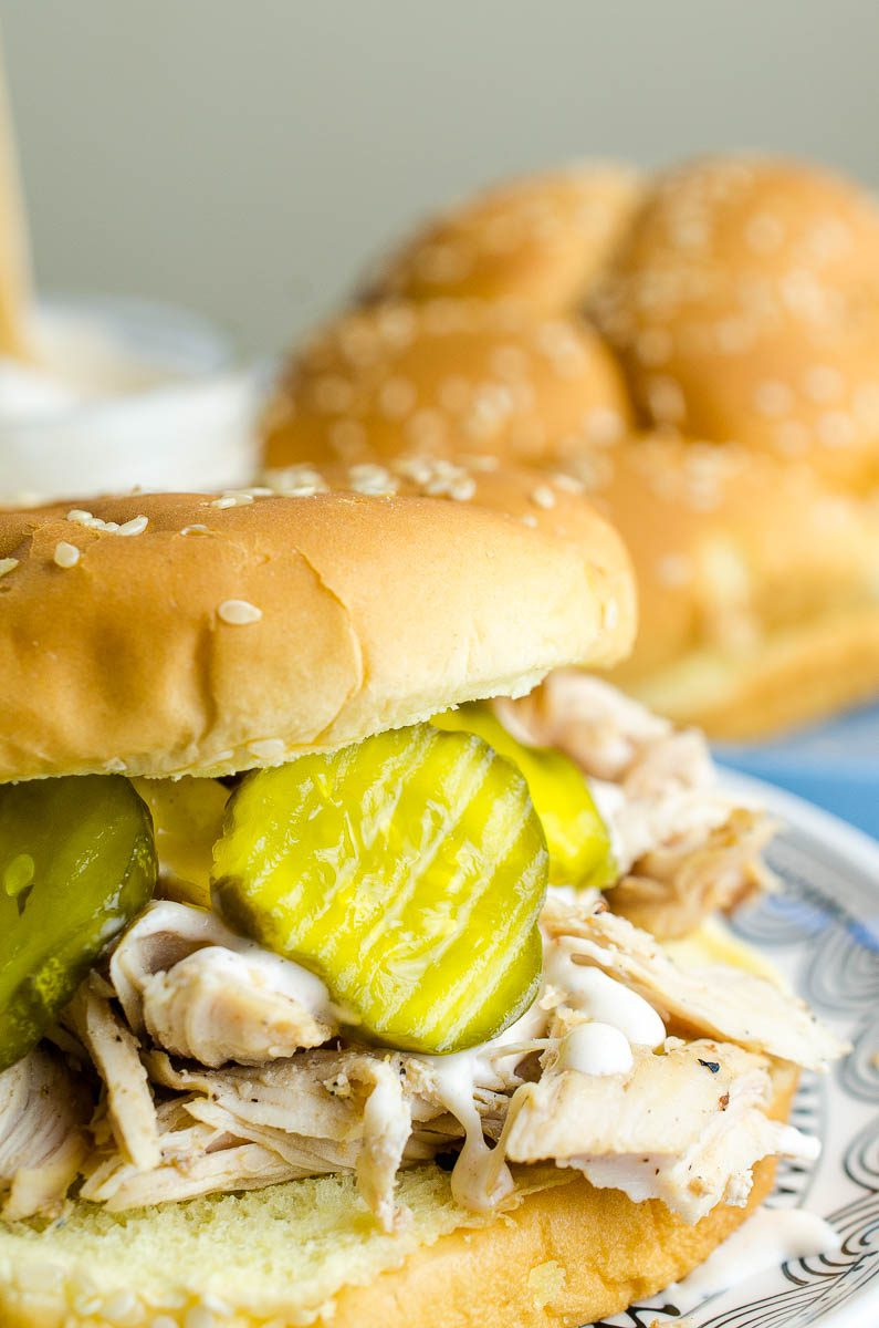 This easy pulled chicken sandwich is made with chicken marinated in Alabama BBQ sauce, grilled, shredded and topped with more Alabama BBQ and bread and butter pickles. The perfect summer sandwich!