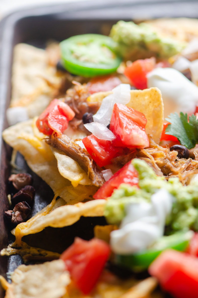 Side view of nachos on a baking sheet.
