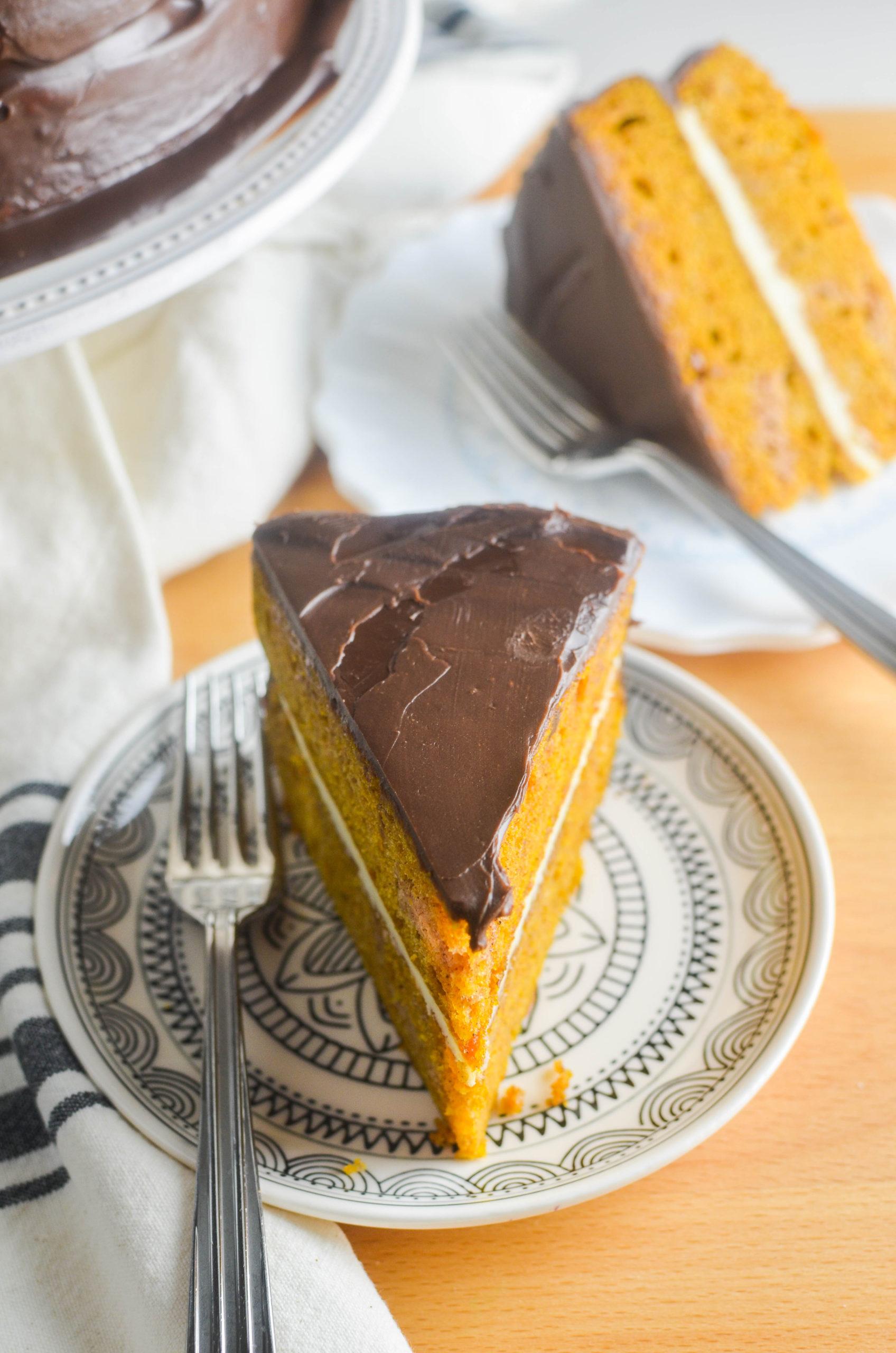 Slice of pumpkin cake with chocolate ganache on a plate.