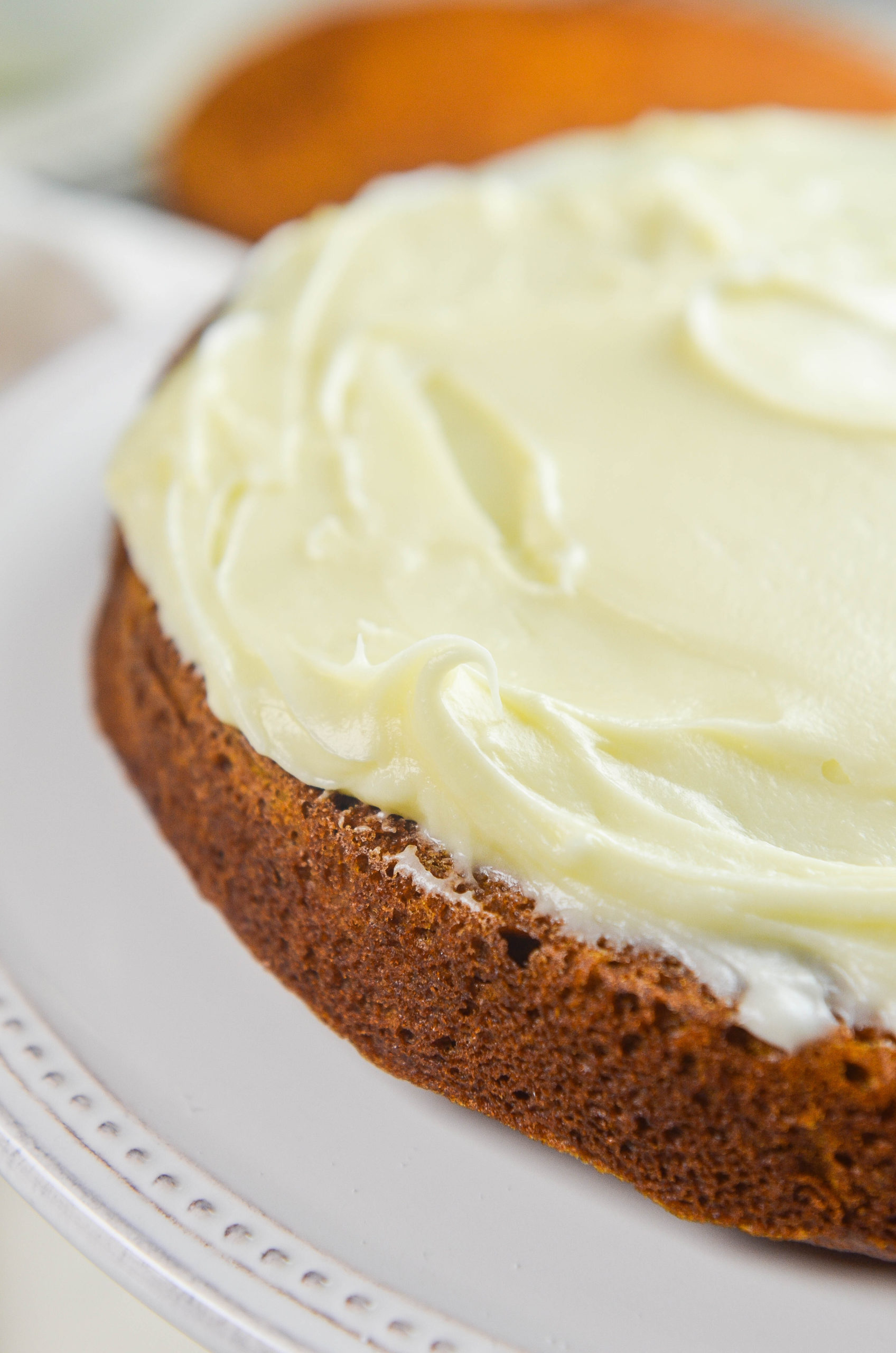 A layer of cream cheese frosting on top of a pumpkin cake.
