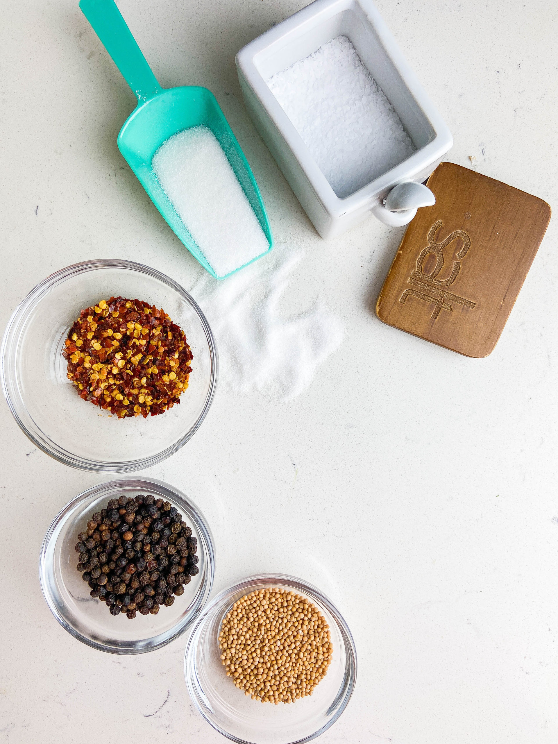 Mustard seeds, black peppercorns, crushed red peppers in glass bowls. Sugar in a teal scooper and salt in a white salt cellar.