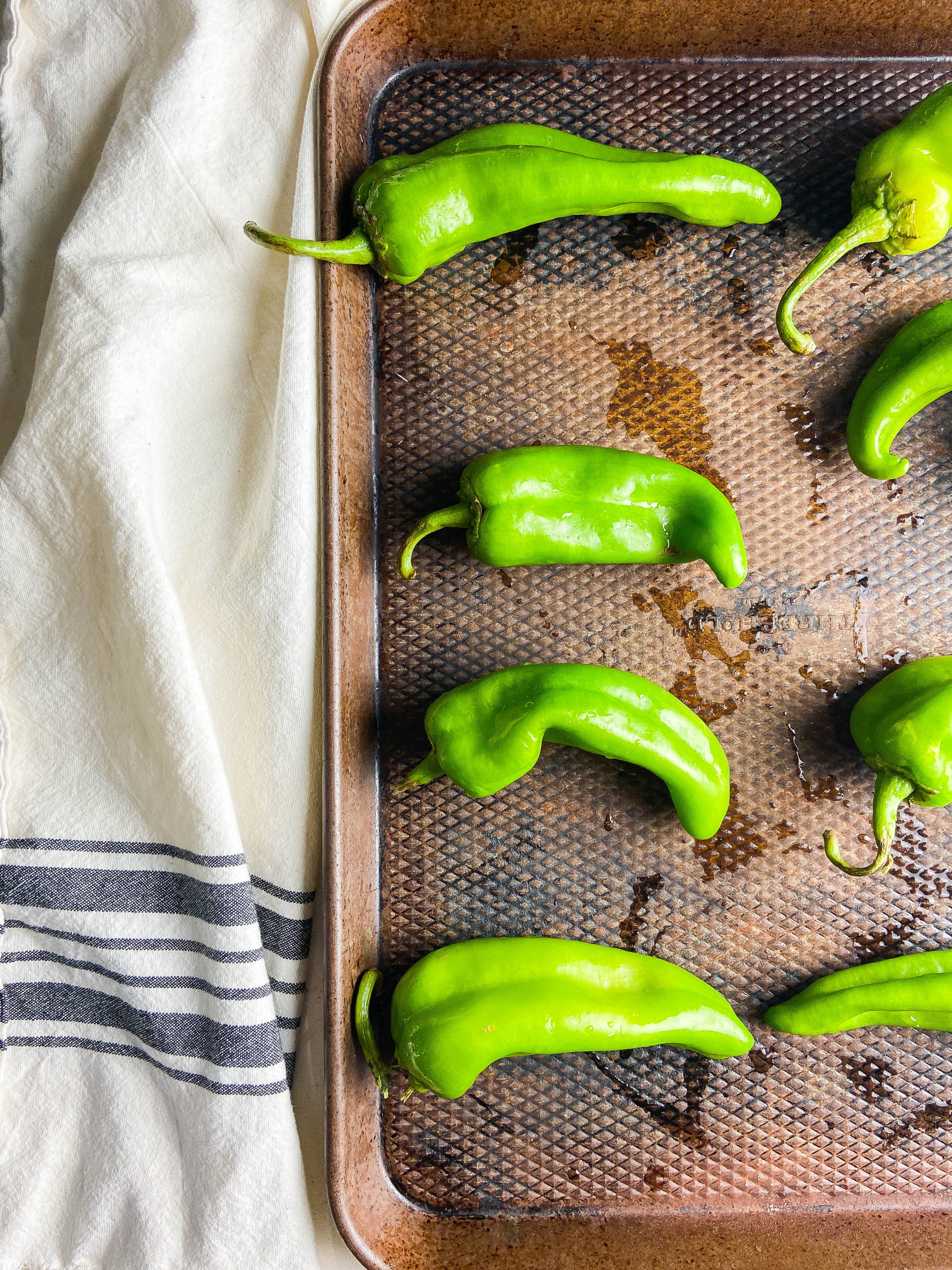 Green chiles on a baking sheet.