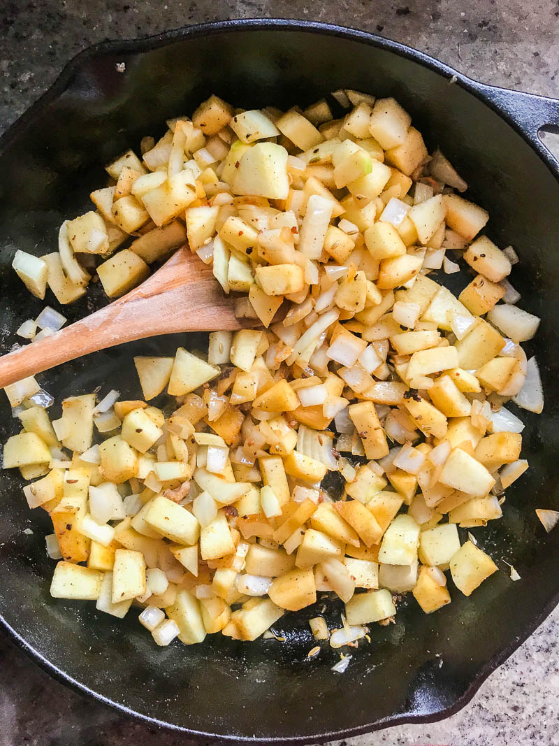 Sauteed apples and onions in a cast iron skillet.