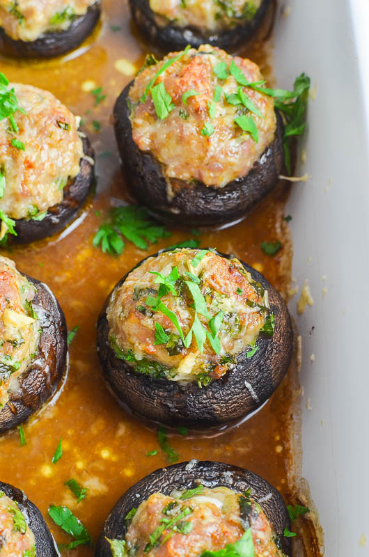 Sausage stuffed mushrooms in a white casserole dish.