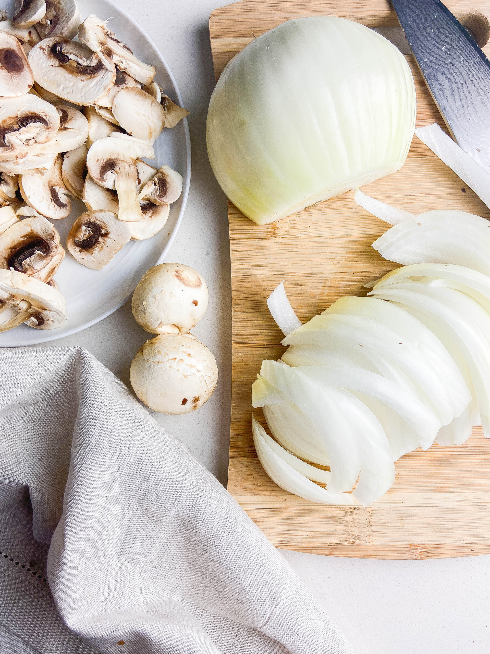 Overhead photo of sliced onions and mushrooms on wooden cutting board.