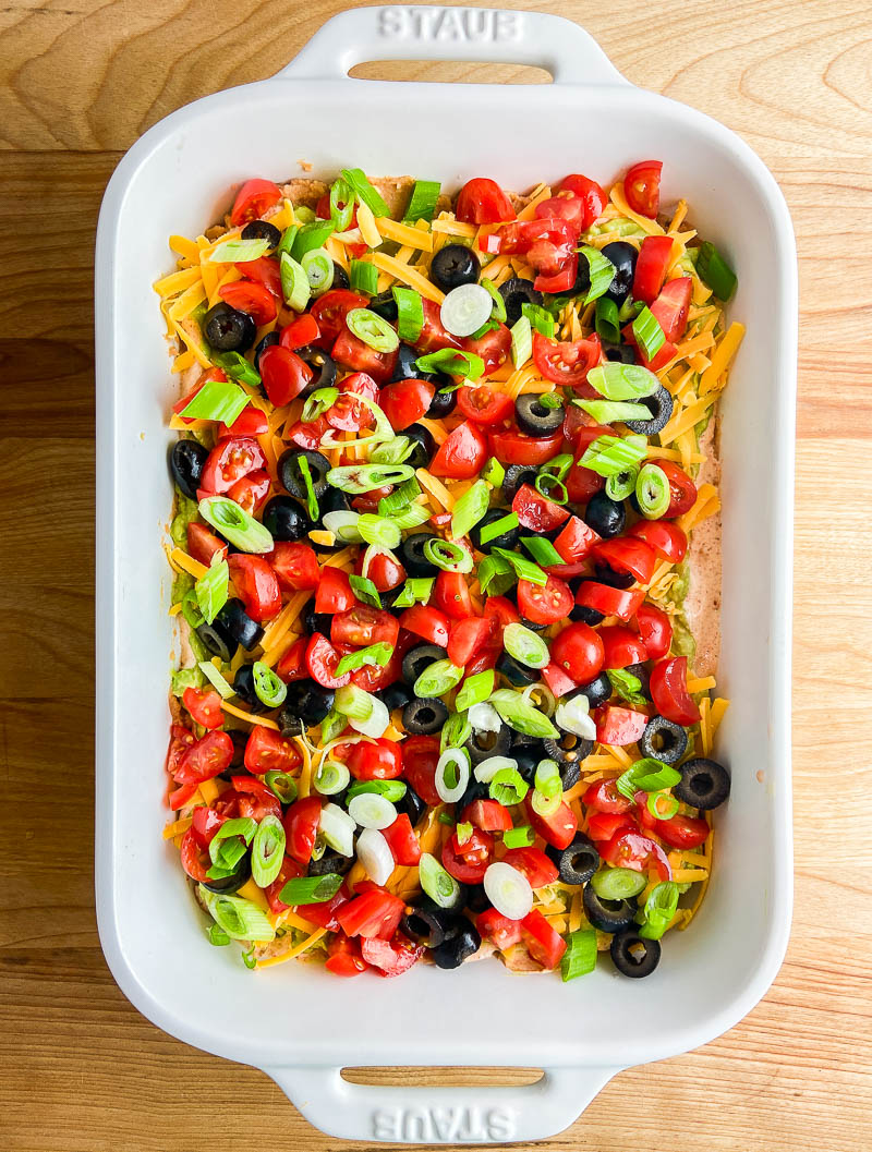 Seven layer dip in a white dish on wooden cutting board.