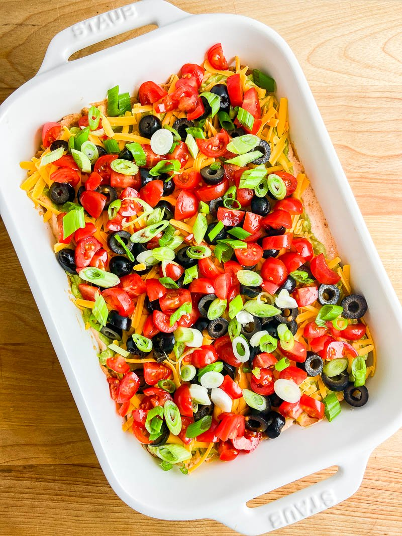 Seven Layer Taco Dip in a white dish on wooden cutting board.