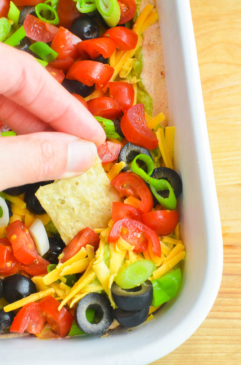 Dipping a chip into taco dip in a white dish.