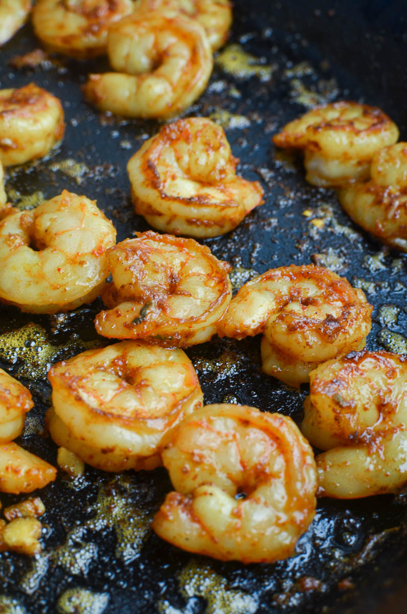 Shrimp cooking in a cast iron skillet.