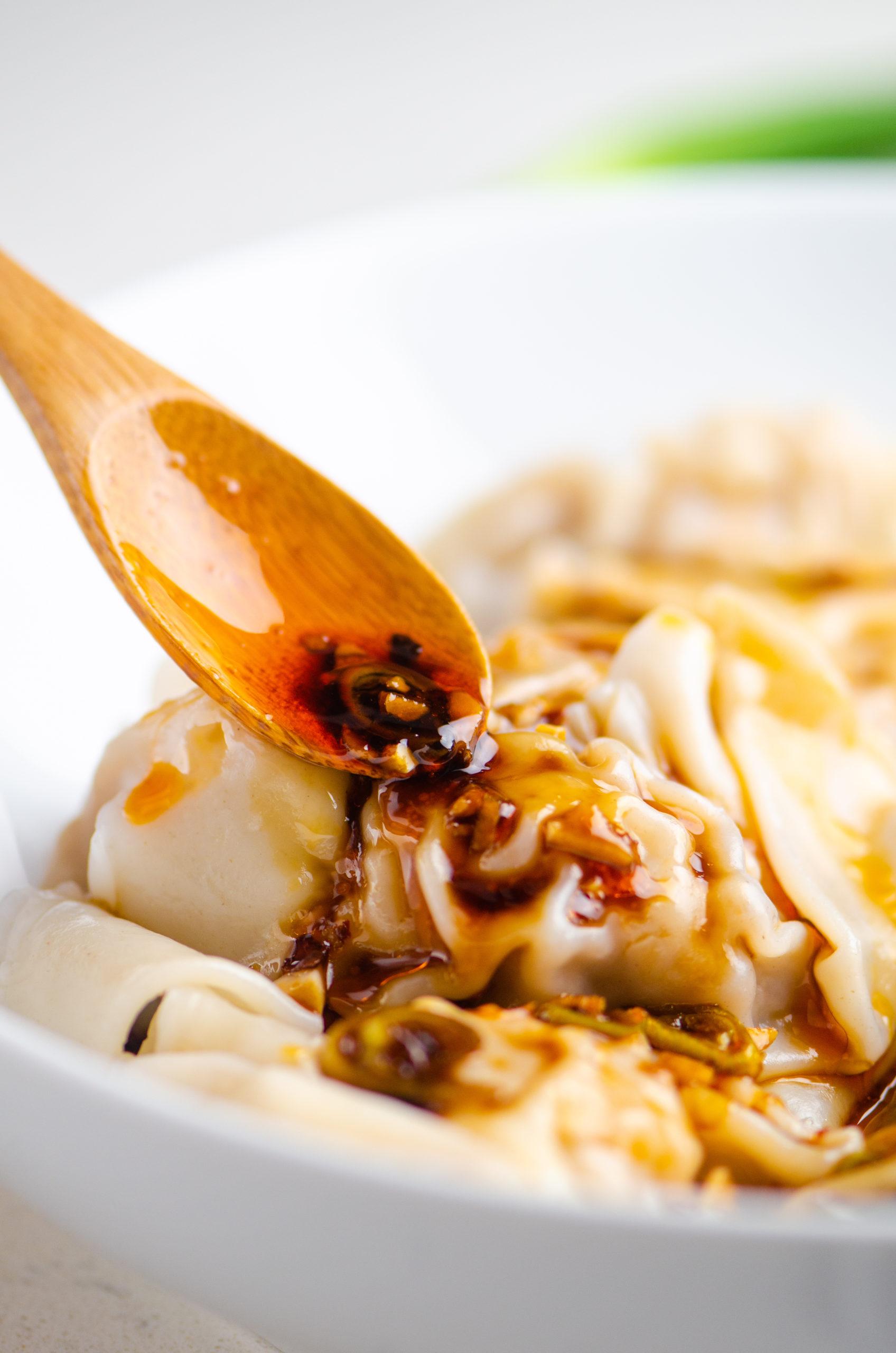 Spooning spicy sauce over the top of dumplings
