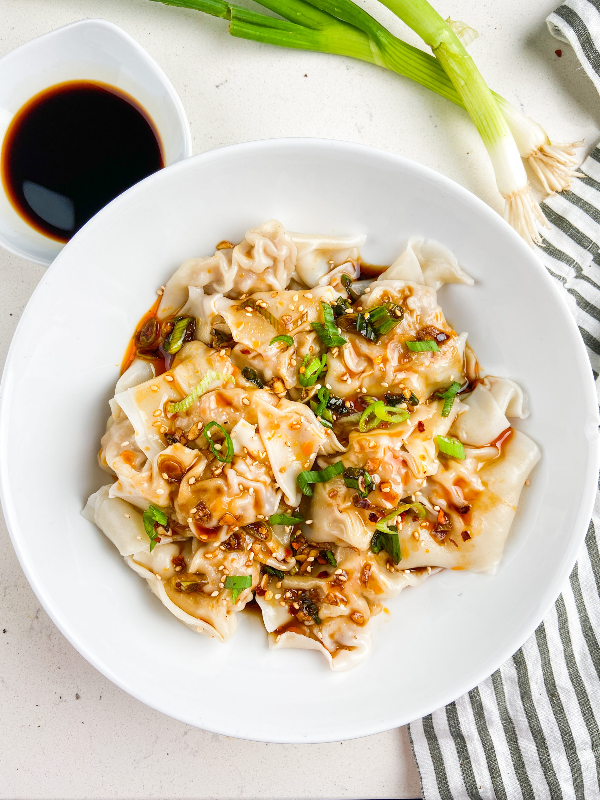 Overhead photo of shrimp and pork wontons in a white bowl.