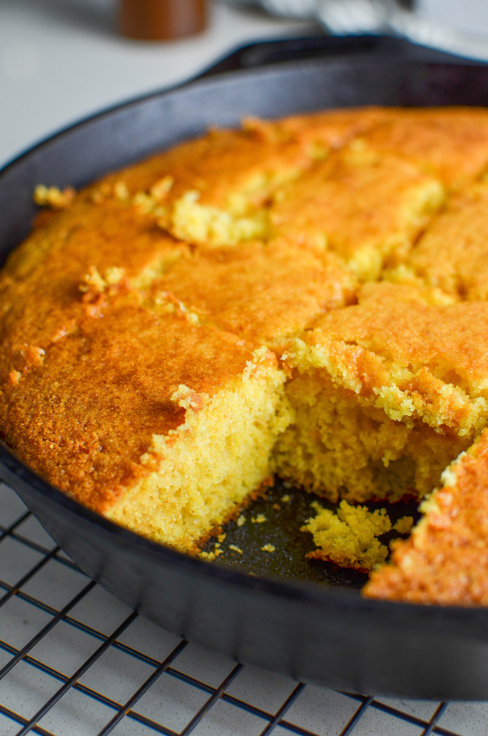 Side angle photo of sliced cornbread in a skillet.