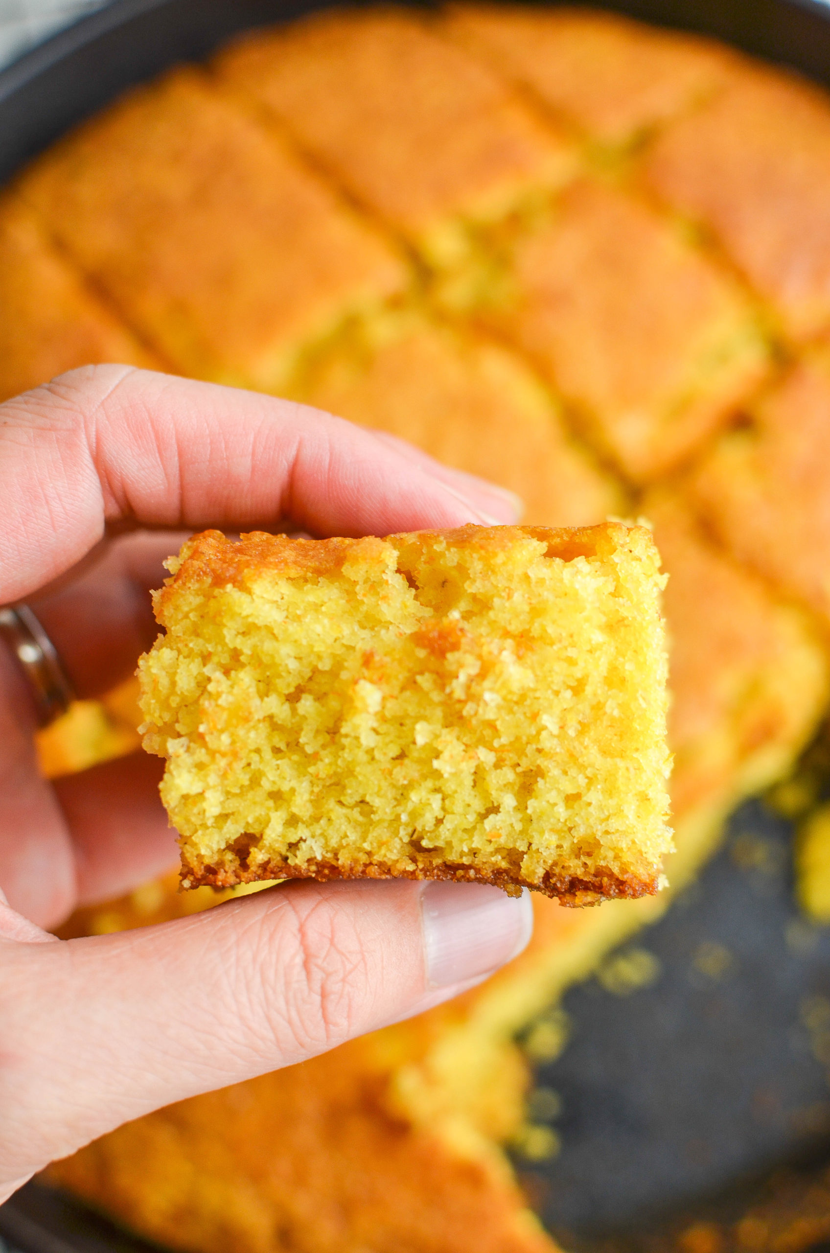 Hand holding a square of cornbread.