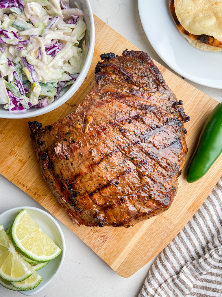 Grilled flank Steak on a cutting board  with coleslaw.