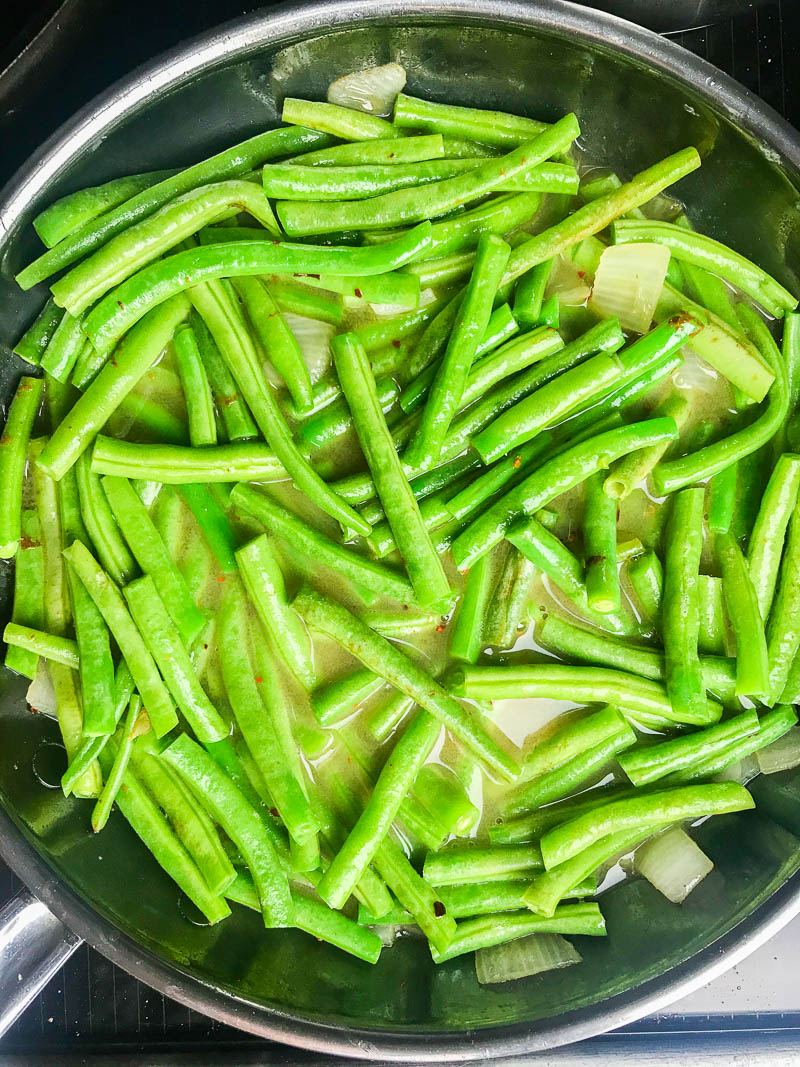 Simmering green beans in chicken broth.