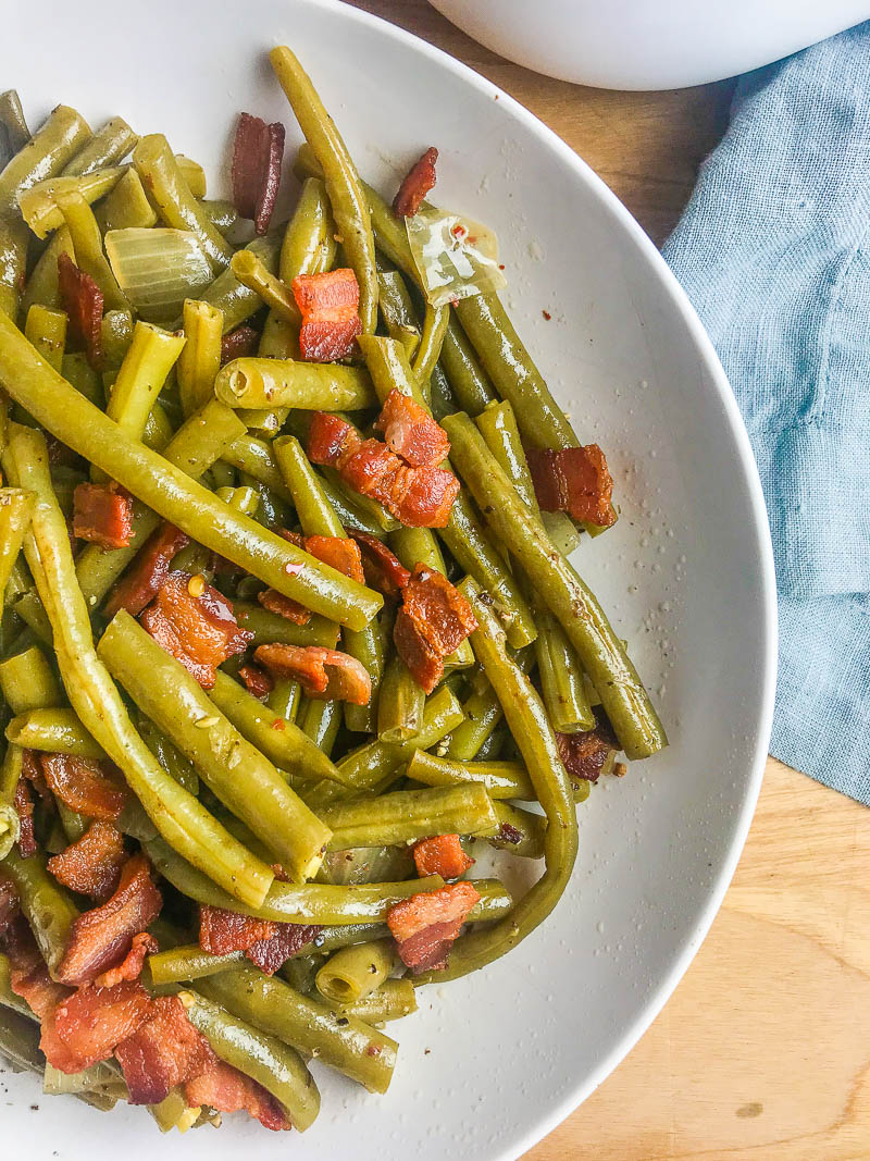 Southern Style Green Beans with Bacon is a comfort food classic. Fresh green beans slow simmered with onions, chicken broth and bacon. Perfect for holidays and Sunday supper!