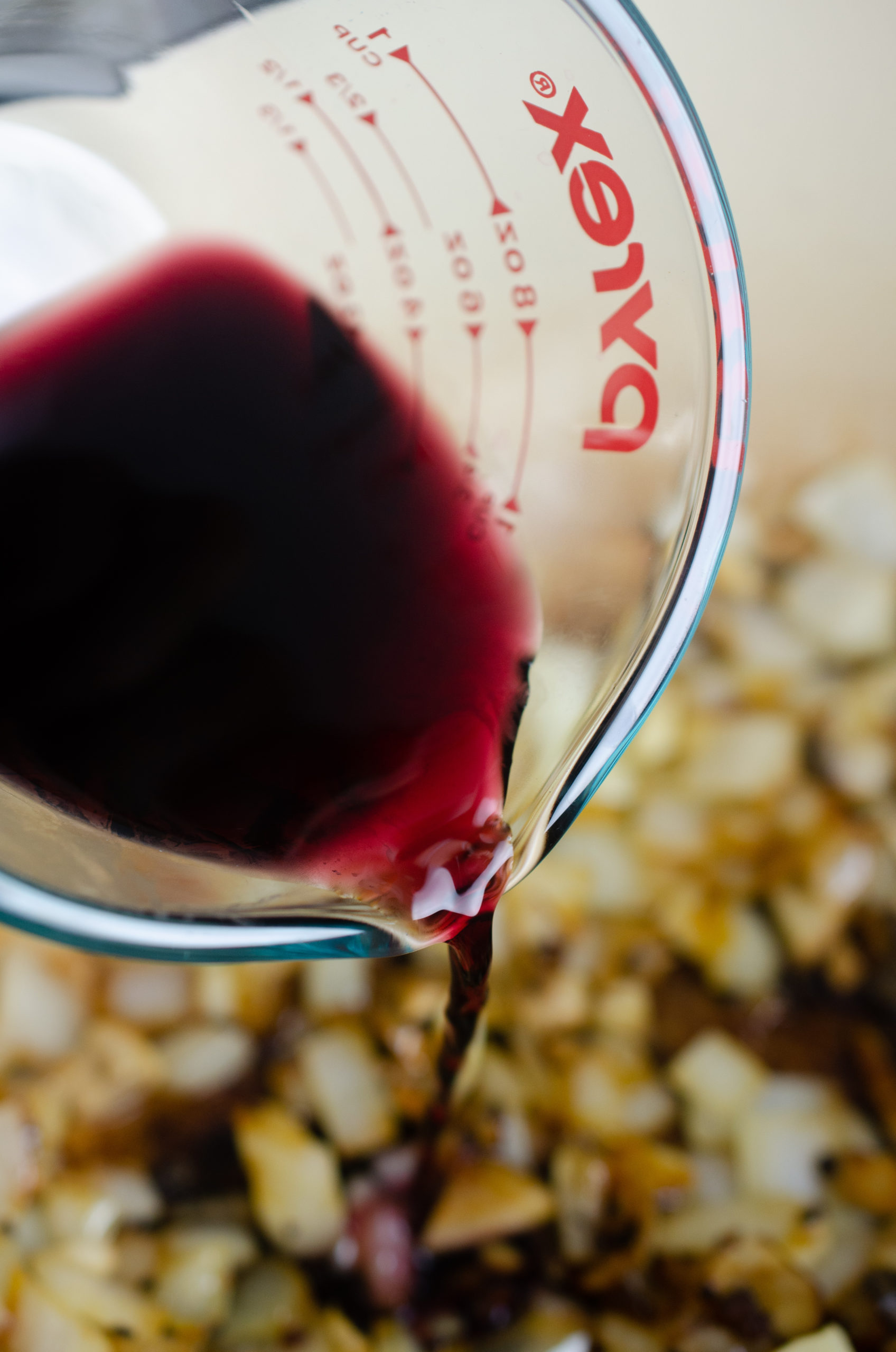 pouring red wine into a pot.
