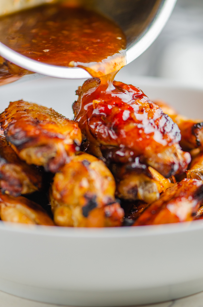 Pouring sweet chili sauce over baked chicken wings.