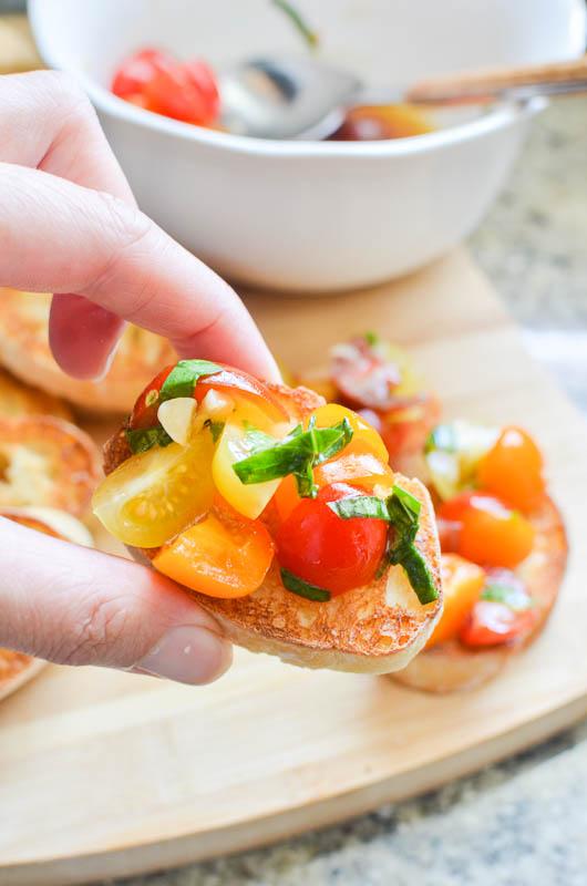 Hand holding tomato bruschetta.