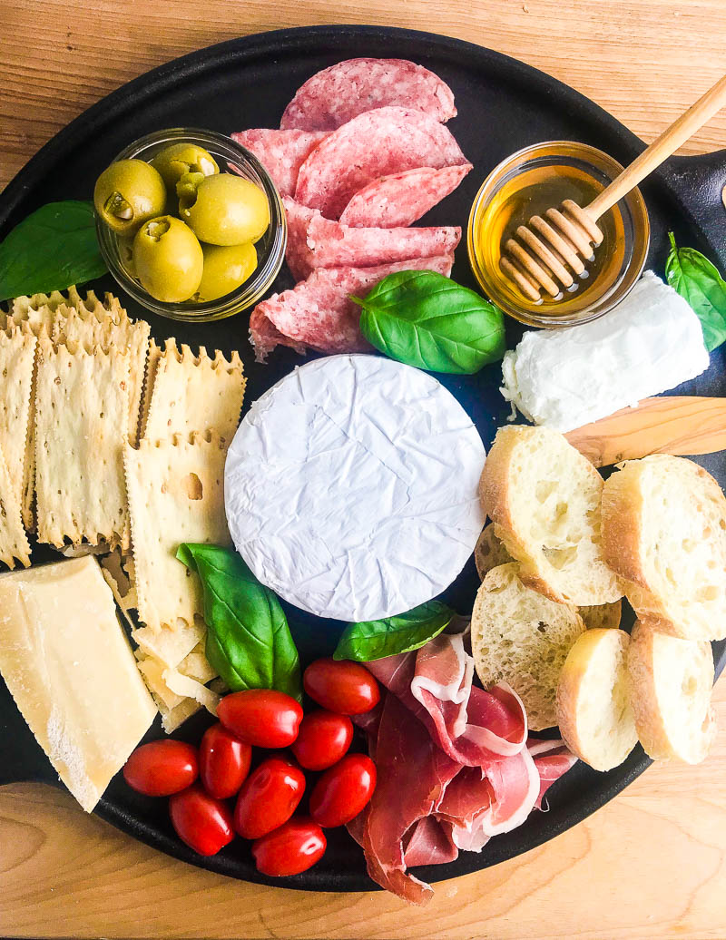 This Summer Charcuterie Board is loaded with 3 different kinds of cheese, meat, olives, tomatoes, crackers and sweet honey. It's perfect for all of your snacking this summer.